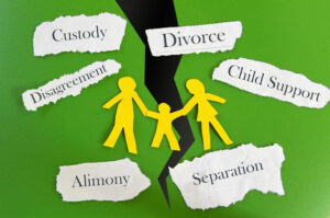 Image of a family of paper dolls holding hands on a green background torn down the middle with several words surrounding it, representing the issues that a Logan County family lawyer can help with when facing a divorce in WV.