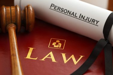 "Image of a scroll labeled ""personal injury"" by a gavel labeled ""lawyer,"" representing how a Logan, WV personal injury lawyer is most qualified to handle local claims and cases."