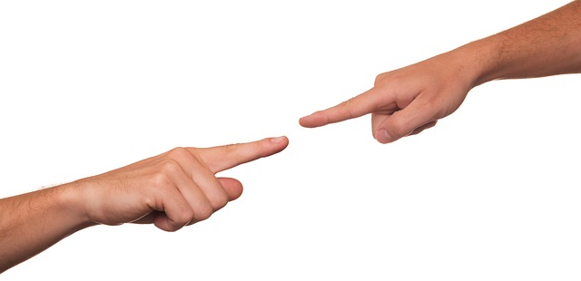 Image of two arms and hands extended with pointer finger of each pointing at each other, showing how a southern WV abuse and neglect defense attorney can help defend you when accusations are made.