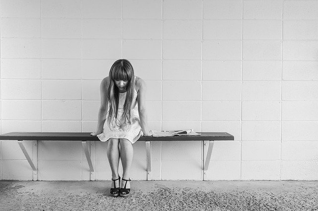 Image of woman on a bench grieving with head bowed, representing how Logan County, WV wrongful death lawyer Jason Harwood can help you obtain a wrongful death settlement.